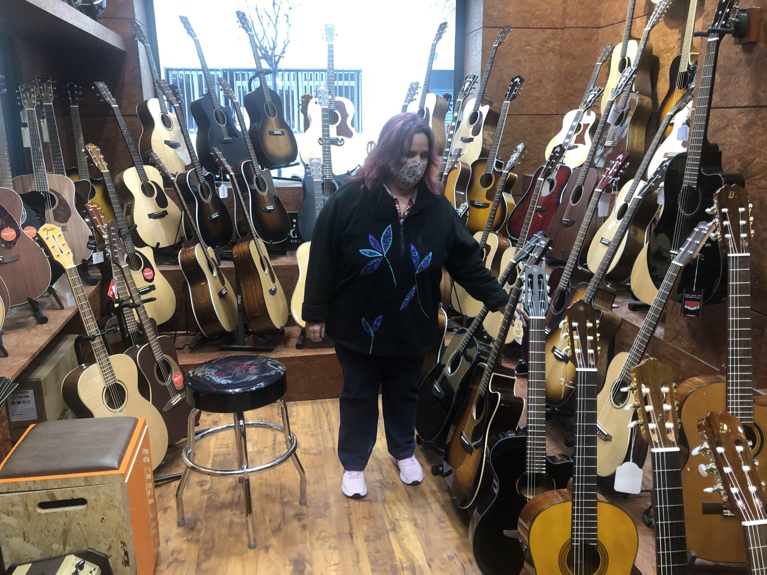 Salvi en una tienda rodeada de guitarras.